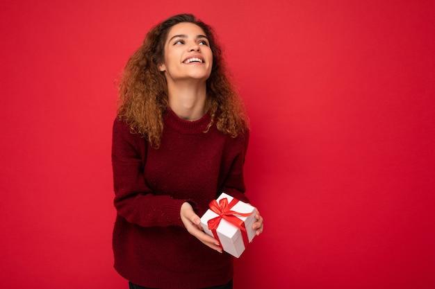 Lockige weibliche person lokalisiert über roter hintergrundwand, die roten pullover hält, der geschenkbox hält, der oben schaut. speicherplatz kopieren, modell