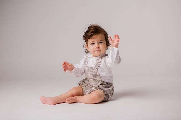 Lockiger brunette des babys 6 monate auf weiß