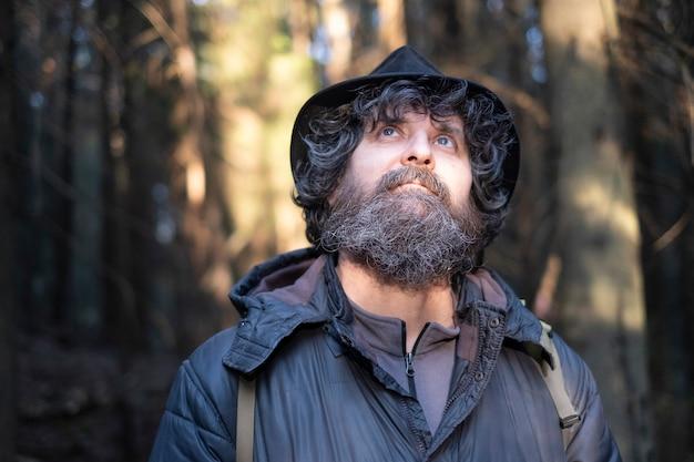 Lockiger erwachsener brünetter mann mit blauen augen mit einem bart in einem hut in einem park oder im wald