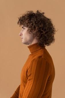 Lockiger haariger mann der seitenansicht mit der braunen bluse, die aufwirft