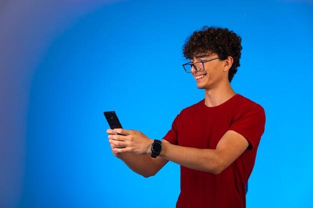 Lockiger haarjunge im roten hemd, der ein smartphone hält.
