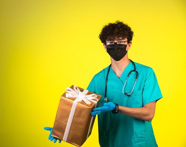 Lockiger haarjunge in der medizinischen uniform und in der gesichtsmaske, die eine geschenkbox hält