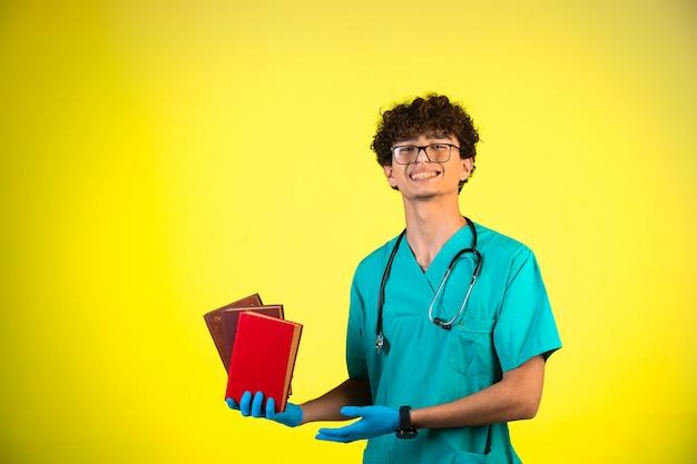 Lockiger junge in medizinischer uniform und handmasken, die seine bücher demonstrieren