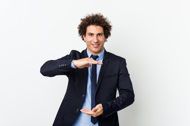Lockiger mann des jungen geschäfts gegen weiße wand, die etwas mit beiden händen, produktpräsentation hält.