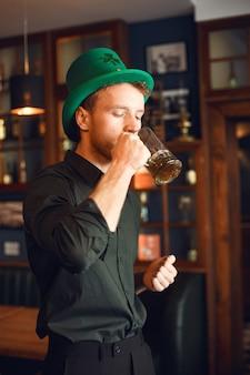 Lockiger mann in einem grünen hut. guy trinkt bier. mann feiert einen feiertag in einer kneipe.