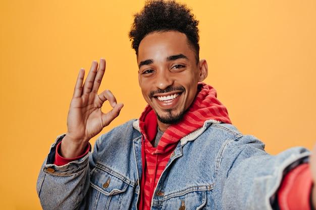 Lockiger mann in jeansjacke zeigt ok-zeichen und macht selfie