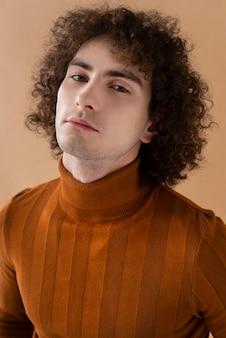 Lockiger mann mit der braunen bluse, die aufwirft