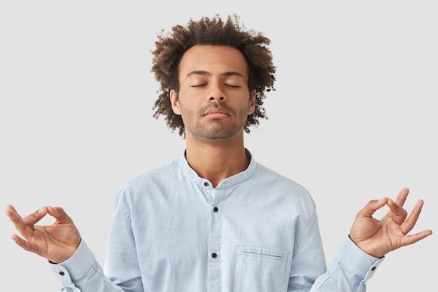 Lockiger mann mit dunkler haut und lockigem haar, im hemd gekleidet, hält die augen geschlossen, hält die hände im mudra-zeichen, genießt eine friedliche atmosphäre