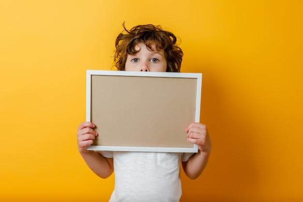 Lockiger niedlicher junge im weißen t-shirt hält einen leeren rahmen für textlächeln und zeigt finger auf hellgelbem oberflächenweißem schild oder banner-kopierraumkonzept, um textnachrichtentafel zu füllen