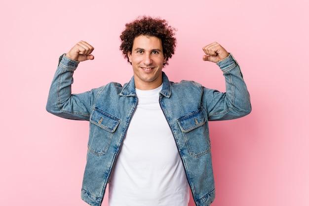Lockiger reifer mann, der eine jeansjacke gegen rosa trägt, die stärke geste mit armen zeigt, symbol der weiblichen kraft