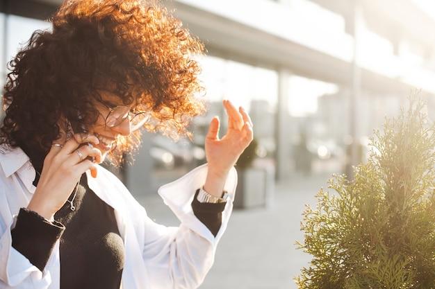Lockiges geschäftsfraulächeln draußen für lifestyle-design-business-technologie urbanen lifestyle lockiges haar