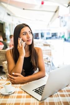 Lockiges lateinamerikanisches mädchen, das am telefon spricht, während sie im straßencafé sitzt. hübsche freiberuflerin in gläsern, die im restaurant abkühlen.