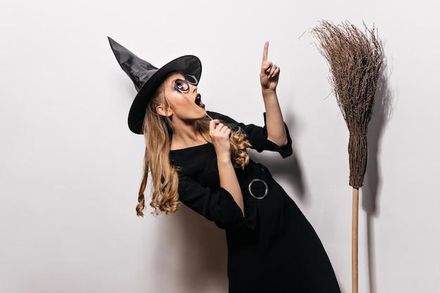 Lockiges mädchen im halloween-kostüm, das oben schaut. charmante hexe im schwarzen hut, der mit altem besen aufwirft.