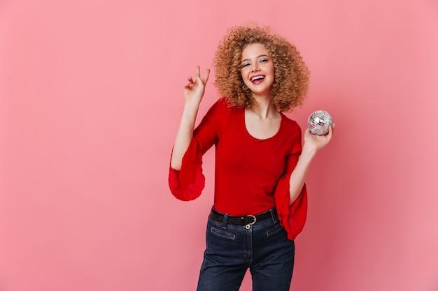 Lockiges mädchen mit charmantem lächeln zeigt zeichen des friedens. dame in rotem langärmeligem oberteil hält discokugel auf rosa raum.