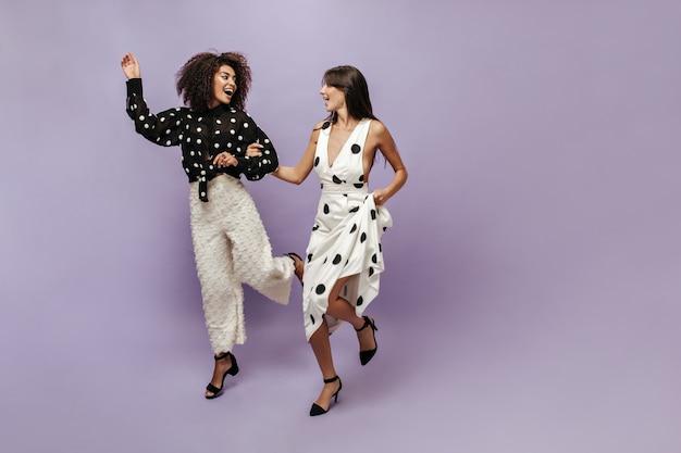 Lockiges stylisches mädchen in langärmeliger schwarzer bluse und weißer weiter hose lacht und sieht ihre freundin in einem leichten modernen kleid an