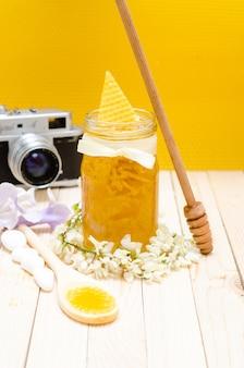 Locust Honey Retro Glas mit Johannisbrotblüten und kleinen weißen Steinen