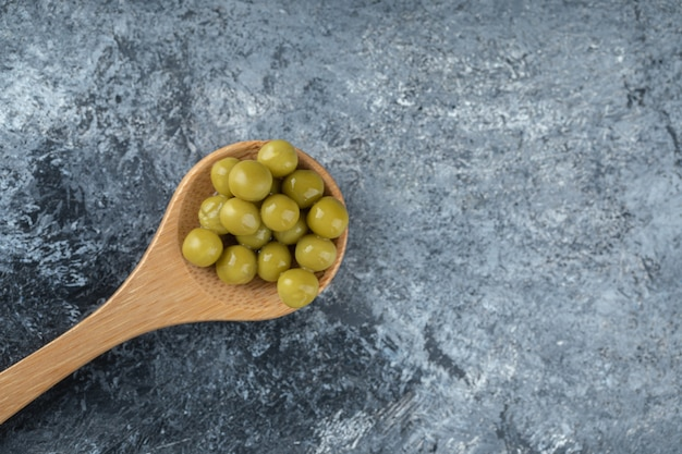 Löffel eingemachte grüne erbsen auf grauem tisch.