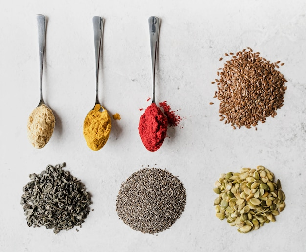 Löffel gefüllt mit verschiedenen samen und lebensmittelpulvern
