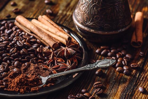 Löffel gemahlener kaffee, kaffeebohnen und einige gewürze auf teller.