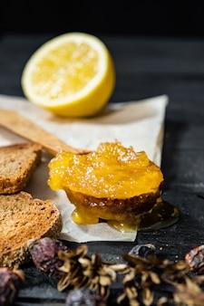 Löffel honig auf dunkler rustikaler oberfläche. kristallisierter selbst gemachter honig im hölzernen löffel, zurückhaltender schuss