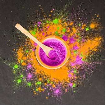 Löffel in der schüssel mit purpurrotem pulver auf tabelle