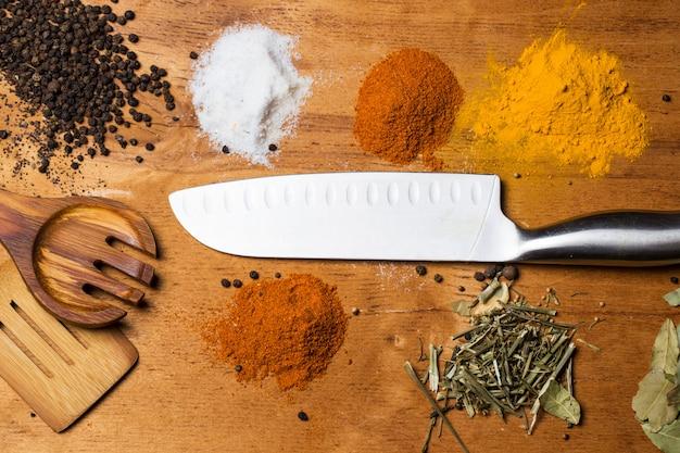 Löffel, messer und haufen von gewürzen auf dem tisch