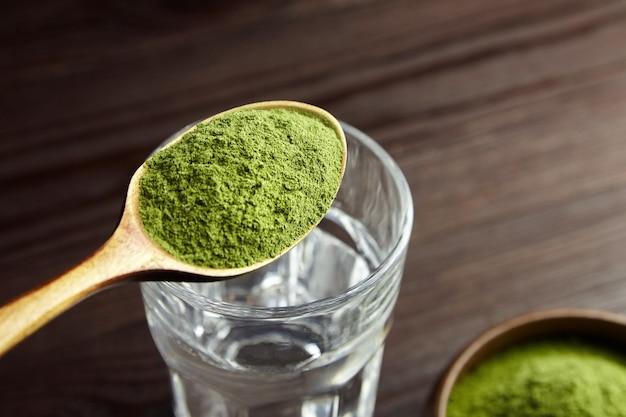 Löffel mit gefriergetrocknetem weizengraspulver für weizengras-entgiftungssaft. gesundes lebensstilkonzept.
