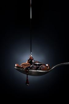 Löffel mit kaffeebohnen und karamell an einer dunklen wand