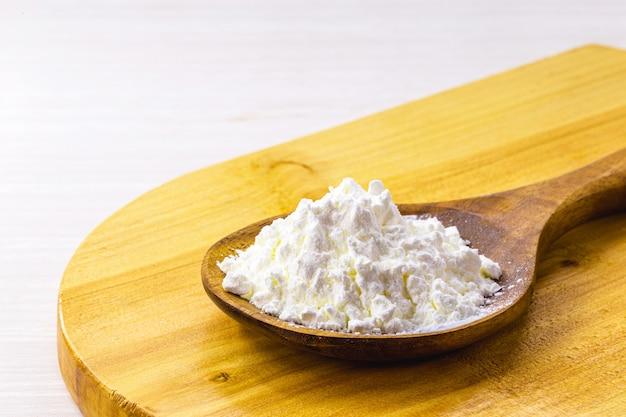 Löffel mit maisstärke, mehl aus mais, das zur herstellung von cremes oder als verdickungsmittel verwendet wird. weiße oberfläche, kopierraum