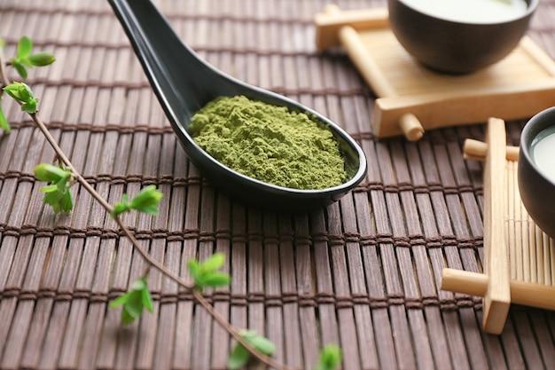 Löffel mit pulverisiertem matcha-grüntee auf bambusmatte