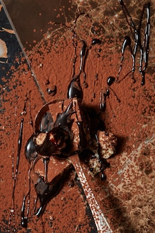 Löffel mit schokolade und pulverkakao auf einer dunklen marmoroberfläche