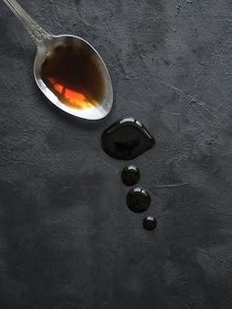Löffel mit undichter sojasauce auf dem schwarzen tisch. pfütze sojasauce.