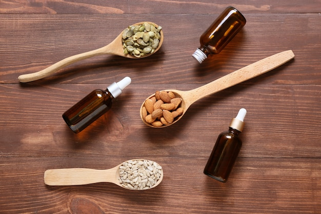 Löffel mit verschiedenen gesunden nüssen und ölflaschen auf holzoberfläche