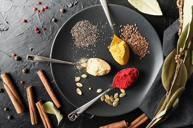 Löffel mit verschiedenen gewürzpulvern in platte