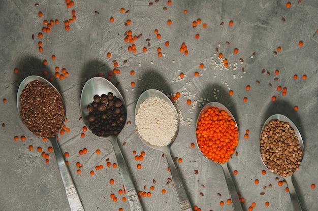 Löffel mit verschiedenen superfoods - leinsamen, sesam, pfeffer, rote linsen, buchweizen auf einer grauen oberfläche. gesundes veganes essen.