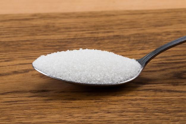 Löffel mit zucker auf holz. gesundheits- und ernährungskonzept