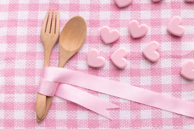 Löffel und gabel auf rosa tischdeckenhintergrund, valentinsgrußtageshintergrund.