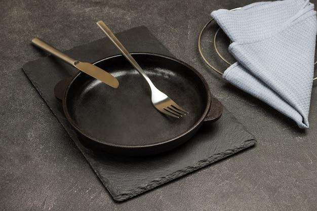 Löffel und gabel in eine leere gusseiserne pfanne geben. graue serviette auf dem tisch. schwarzer hintergrund. ansicht von oben