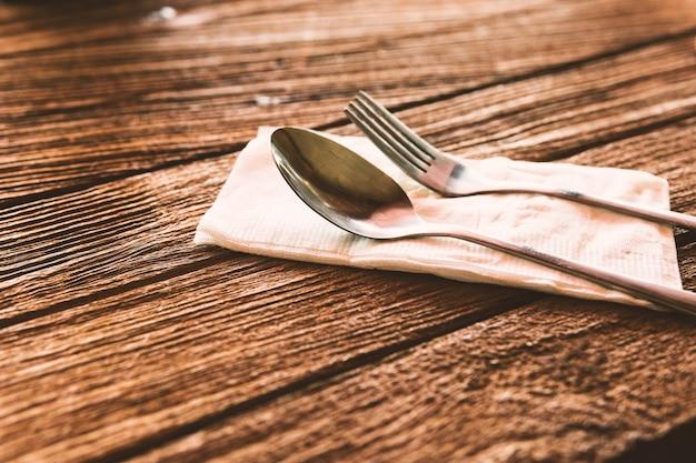 Löffel und gabel setzen auf papier mit hölzernem boden.