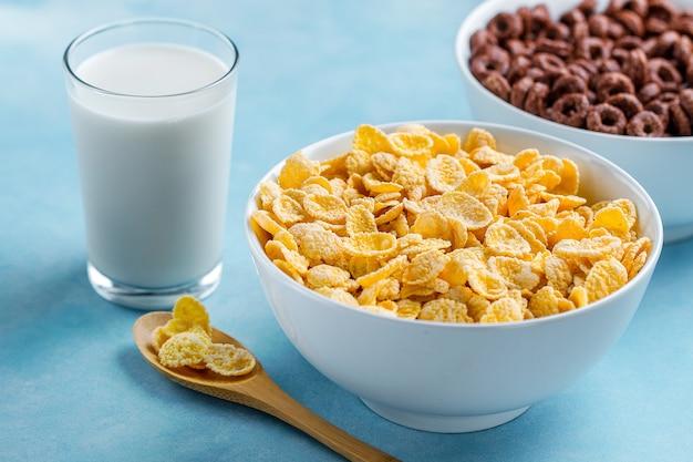 Löffel und schüssel mit schokoladenringen, gelb bereiften corn flakes und einem glas milch zum trockenes, getreidefrühstück