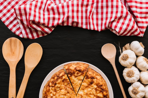 Löffel und serviette nahe knoblauch und torte