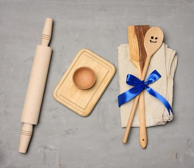 Löffel und spatel gebunden mit blauem band auf grauem hintergrund und hölzernem nudelholz, draufsicht