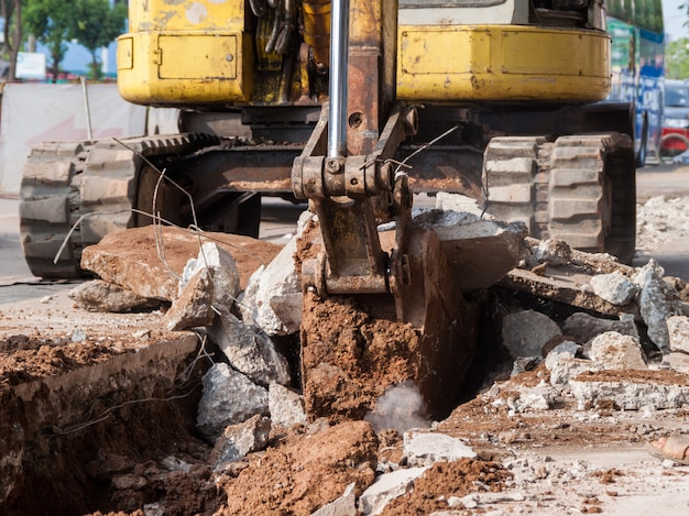 Löffelbagger, der durch konkreten boden gräbt