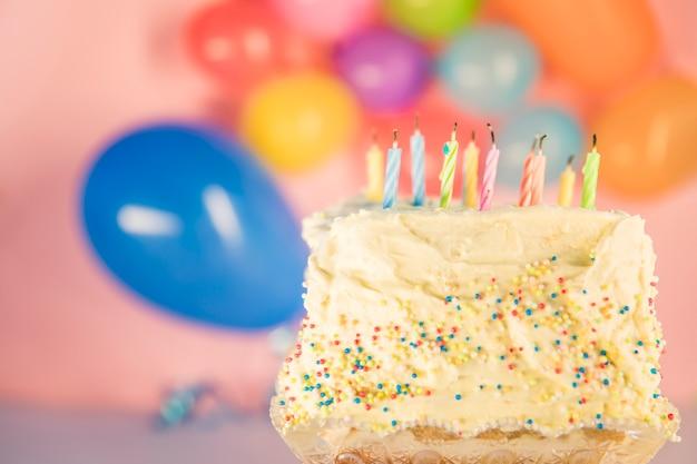 Löschen von kerzen auf kuchen mit unscharfen ballons