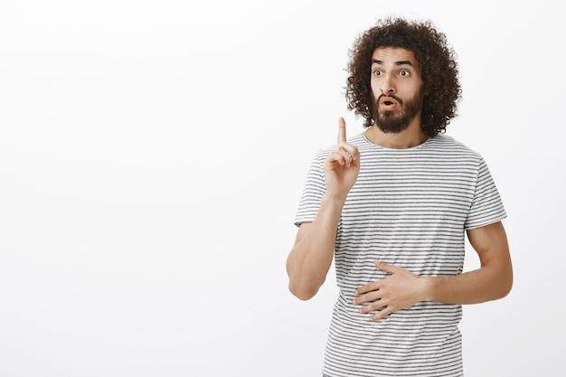 Lösung gefunden. schlauer, gut aussehender erwachsener mitarbeiter mit bart und afro-haarschnitt, der den zeigefinger in der eureka-geste hebt