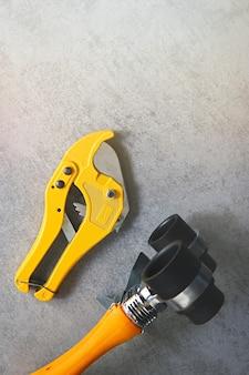 Lötkolben für pvc-rohre und rohrschneideschere sanitärwerkzeuge für die wasserversorgung auf grau Premium Fotos