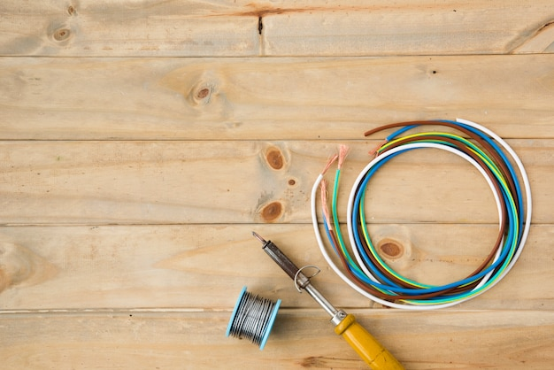 Lötkolben und lötdraht mit buntem kabel auf holzoberfläche