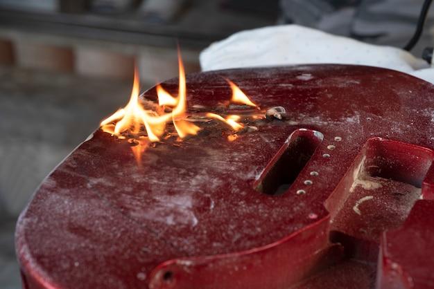 Lötlampenflamme brennt auf fester roter gitarre.