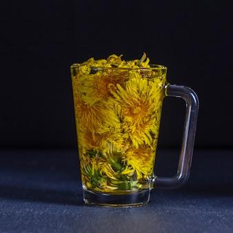 Löwenzahn gelbe blume teegetränk im glas, nahaufnahme. konzept der gesunden ernährung. kräutertee in glastasse und blumen auf schwarzem hintergrund
