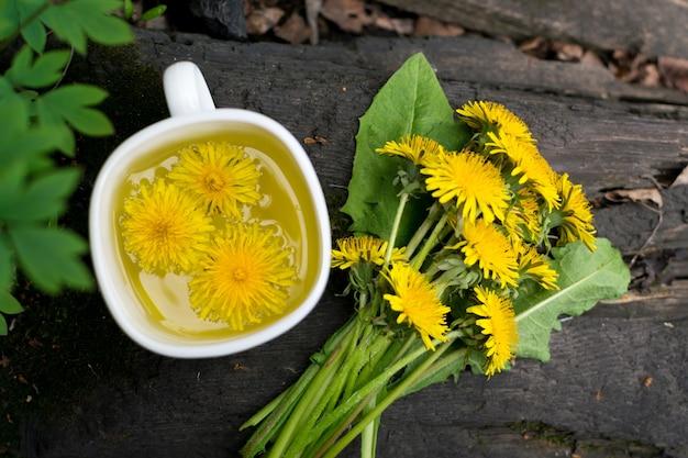 Löwenzahnblumentee-aufguss in der weißen tasse nah oben. kräutergetränk, gelbe blüten und blätter tisane auf natürlichem dunklem hintergrund